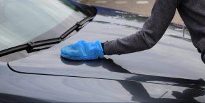 Autolack polieren mit Mikrofaserhandschuh Frau Motorhaube