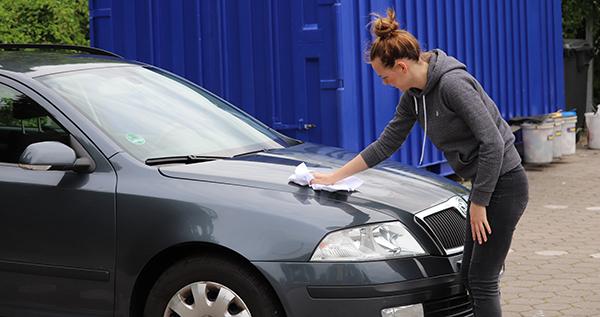 Schöne Frau versiegelt Auto im Lackversiegelung Test